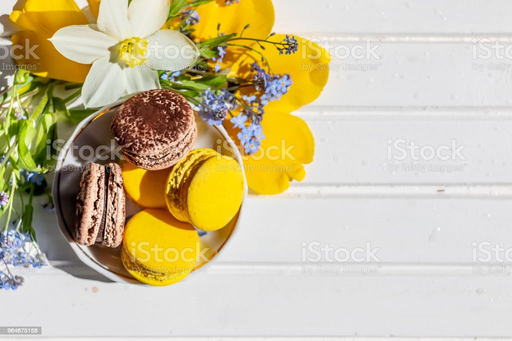 macarons or macaroons dessert sweet beautiful to eat. chocolate and lemon desserts on a white wooden table.Tasty dessert flat lay and daffodils and forget-me-not flowers. royalty-free stock photo