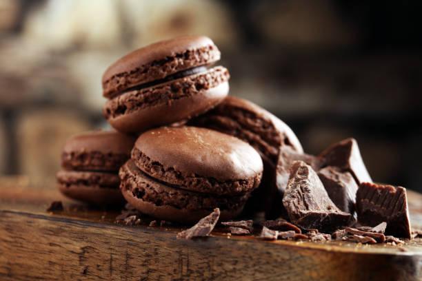 macarons macaron de chocolate doce francês na mesa de madeira - macaroon - fotografias e filmes do acervo
