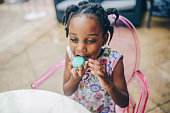 Adorable, 4 year old African American girl eats a bright, delicious pastry, a French Macaroon, in an outdoor cafe type area. She is sitting in a pink chair and is happy and excited about her treat.