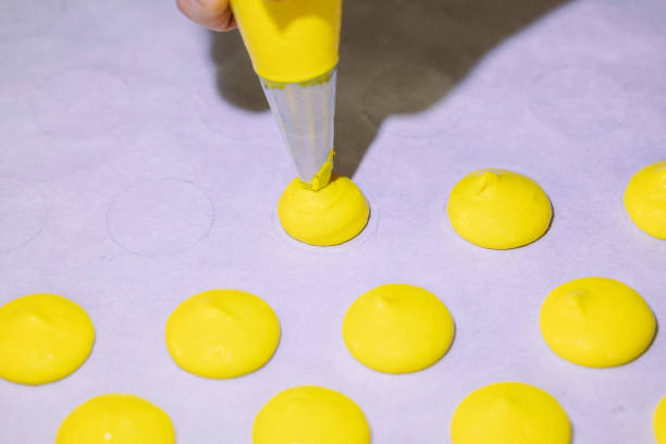 macaroon preparation with a socket on a baking sheet stock photo