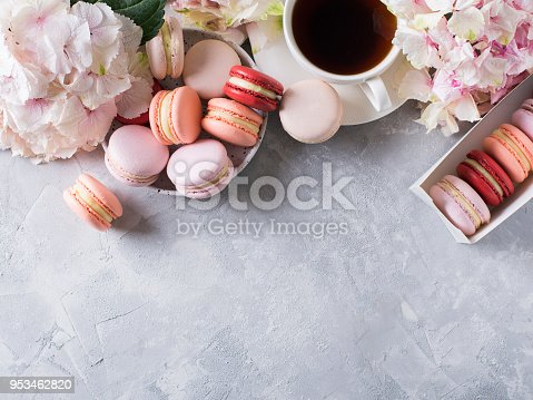 istock Macaroons and cup of coffee with flowers over white texture 953462820