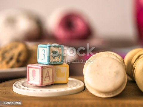 Macaroons and toy blocks on table in soft focus