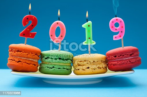 Macaroons on plate with birthday candles isolated on blue