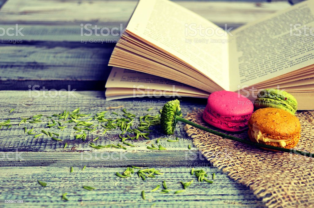 Macaroons with open book on a wooden background stock photo