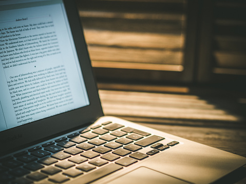 Macbook Air Laptop Beside Wooden Window With Rays Of Light Foto de stock y más banco de imágenes de Anochecer