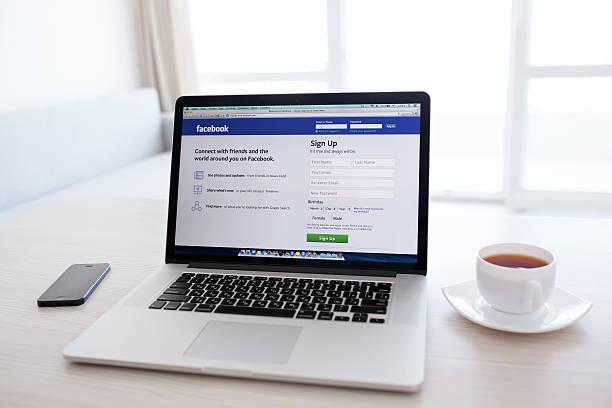 macbook pro retina mit facebook-homepage auf dem bildschirm - www kaffee oder tee stock-fotos und bilder