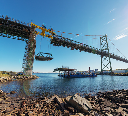 The first section of old deck is lowered from the Angus L. MacDonald Bridge to a waiting barge below.  The re-decking project will replace an additional 45 segments of decking and wrap up in 2017.