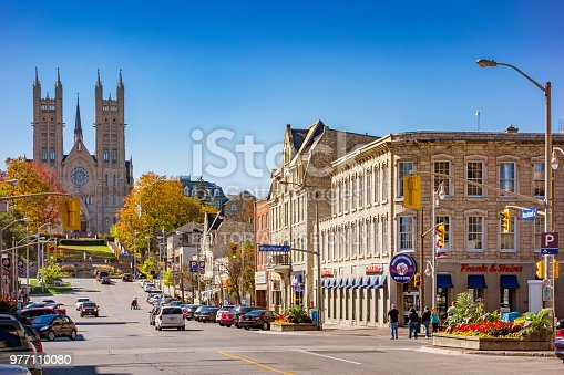 People walk along Macdonell street in downtown Guelph Ontario Canada on a sunny day, with the Basilica of our Lady Immaculate in the background.