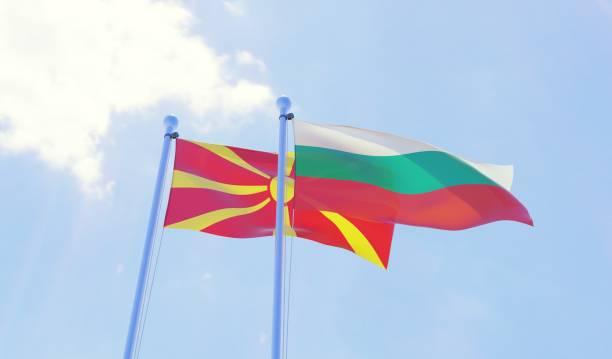 macedonië en bulgarije, twee vlaggen zwaaien tegen blauwe hemel - bulgarije stockfoto's en -beelden