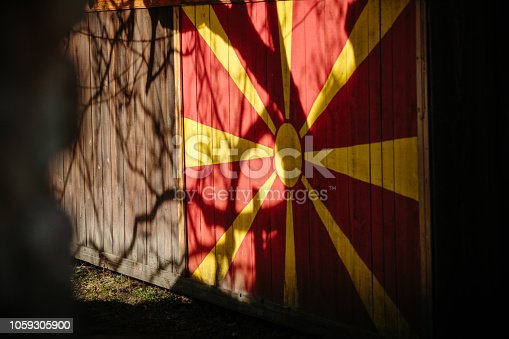 Macedonian flag painted on wooden wall. Tree shadows, sunny day. Republic of Macedonia official symbol. Shadow play. Sun flag. Solar symbol. Official state flag.