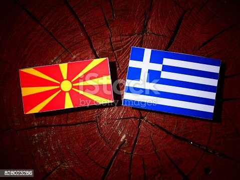 1056280906istockphoto Macedonian flag with Greek flag on a tree stump isolated 828023286