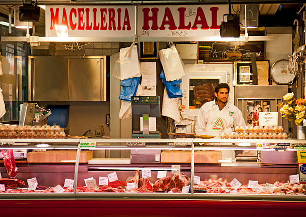Macelleria Halal butcher stall, mercato centrale, Florence Florence, Italy - November 3, 2011: Young butcher at his halal stall in the Mercato Centrale in Florence. His stall sells eggs and chicken and beef cuts. mercato stock pictures, royalty-free photos & images