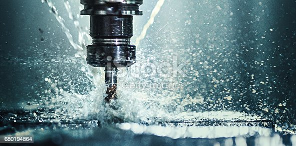Closeup shot of a CNC machine processing a piece of metal. There are three water streams splashing the object to cool it down.