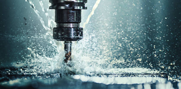 CNC machine drill. Closeup shot of a CNC machine processing a piece of metal. There are three water streams splashing the object to cool it down. drill stock pictures, royalty-free photos & images