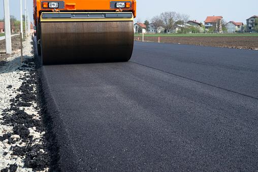 Machine flattening new layer of asphalt. Road construction.