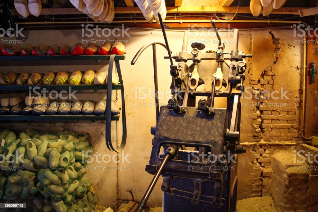 Machine for manufacturing wooden shoes Klompen in Holland. National traditional Dutch wooden shoes. Clog and Klomp Production Workshop. stock photo