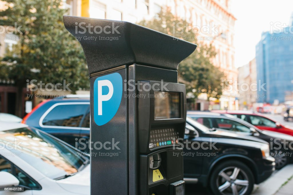 Machine for paying parking. Close-up - machine for paying parking on background of blurry cars stock photo