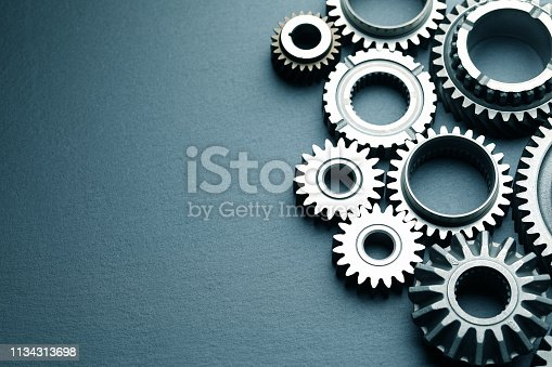 Mechanical gears on black slate background; top view
