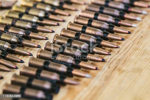 istock machine gun ammo on a wooden table, bullet belt, bandoleer, chain of ammo on wooden background,cartridge 7.62 mm caliber 1132644985