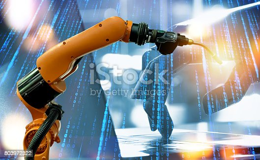 istock Machine learning and artificial intelligence technology concept. Blue tone of binary coded number and robot hand , laptop and automate wireless spot welding machine robot arm in smart factory. 803972322