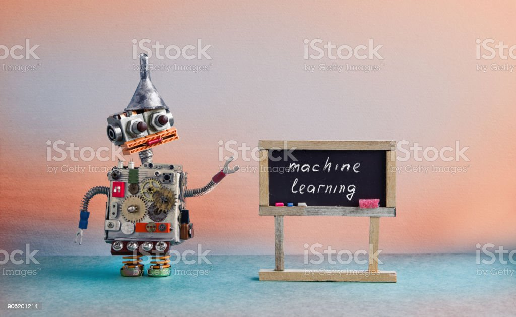 Machine learning concept. Robot creative design toy metal funnel hopper, cogs wheels gears metallic body. Black chalkboard classroom interior, futuristic colors background - foto stock