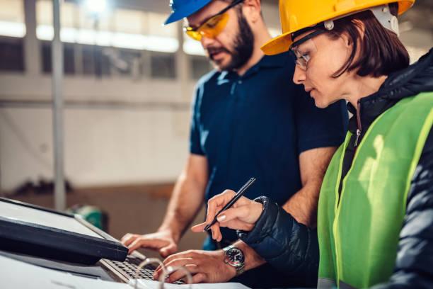 CNC-Maschinenbetreiber und Industrietechniker tippen Fertigungsprogramm für das Schneiden – Foto