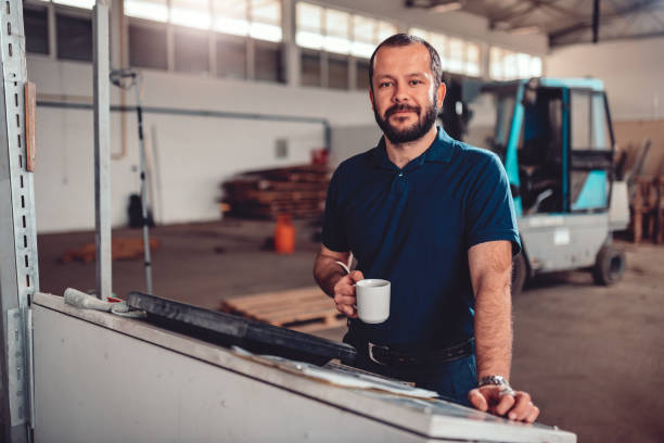 CNC Machine Operator having coffee brake CNC Machine Operator wearing blue shirt having coffee brake in industrial factory one man only stock pictures, royalty-free photos & images