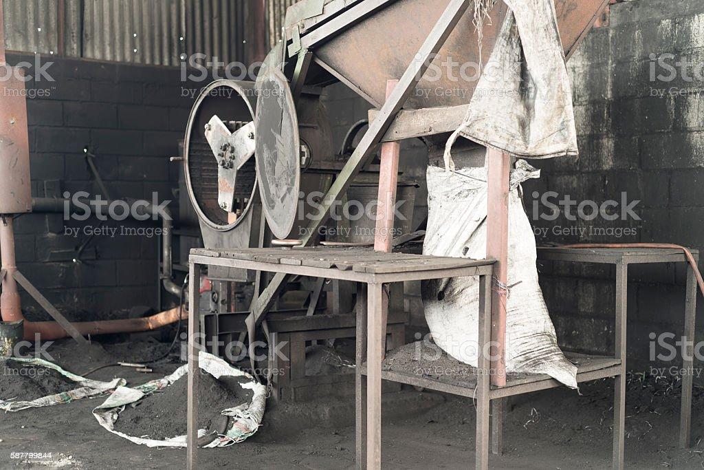 Machine with drum for powderizing carbonized coconut shells stock photo