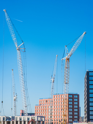 Machinery at construction site. Tall tower cranes with truss construction. Building new house in city. London, UK.