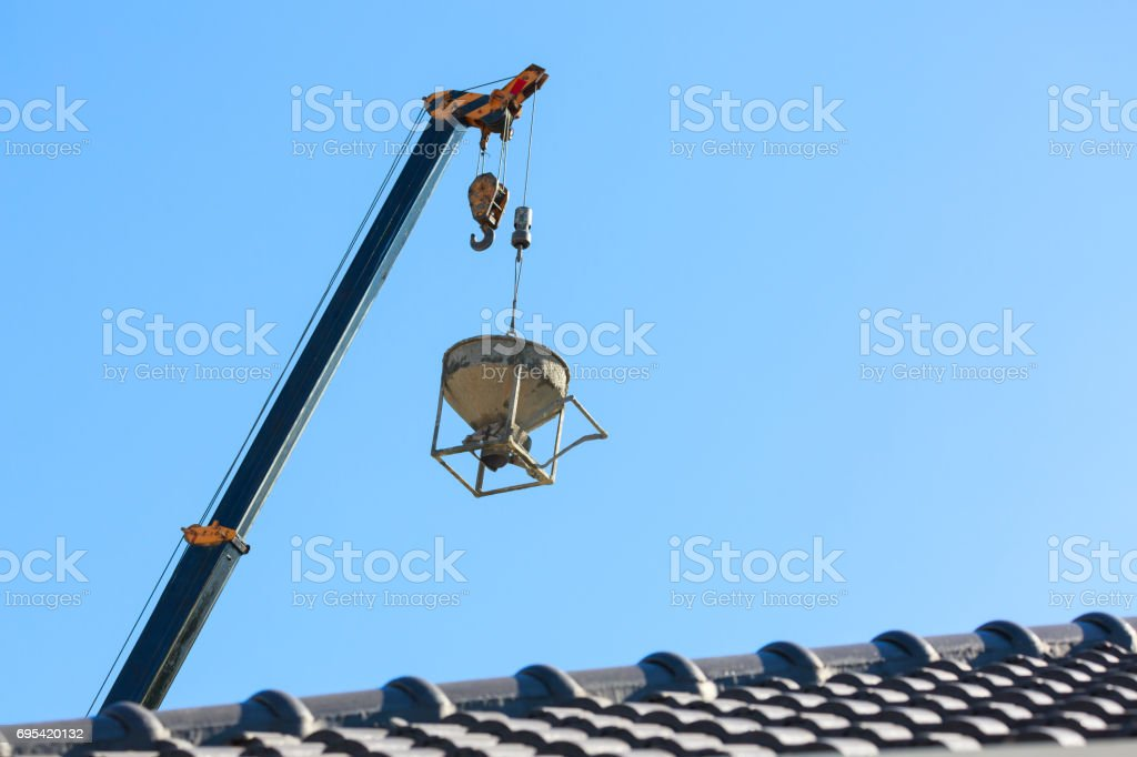 machinery crane hoisting cement mortar mixer bucket container in construction site building industry stock photo