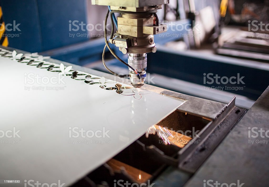 Machinery cutting intricate shapes out of steel sheet stock photo
