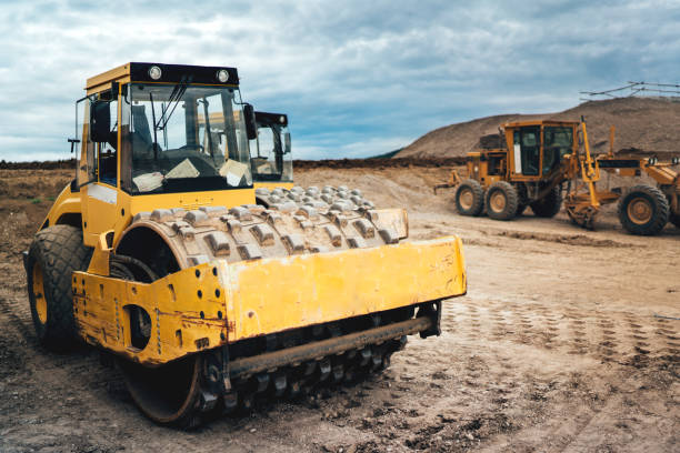 machinery working on highway construction site. Bulldozer, dumper truck, soil compactor and vibratory roller heavy duty machinery working on highway construction site. Bulldozer, dumper truck, soil compactor and vibratory roller compactor stock pictures, royalty-free photos & images