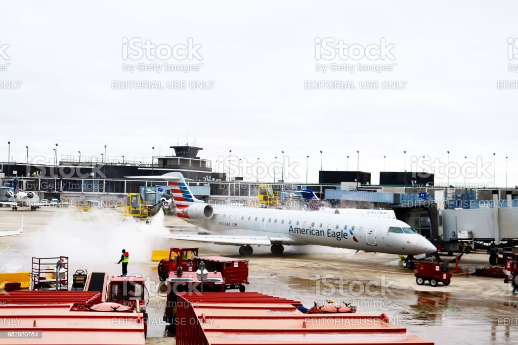 Machines with cranes de-ice an airplane wing at OHare Airport Chicago Illiniois stock photo
