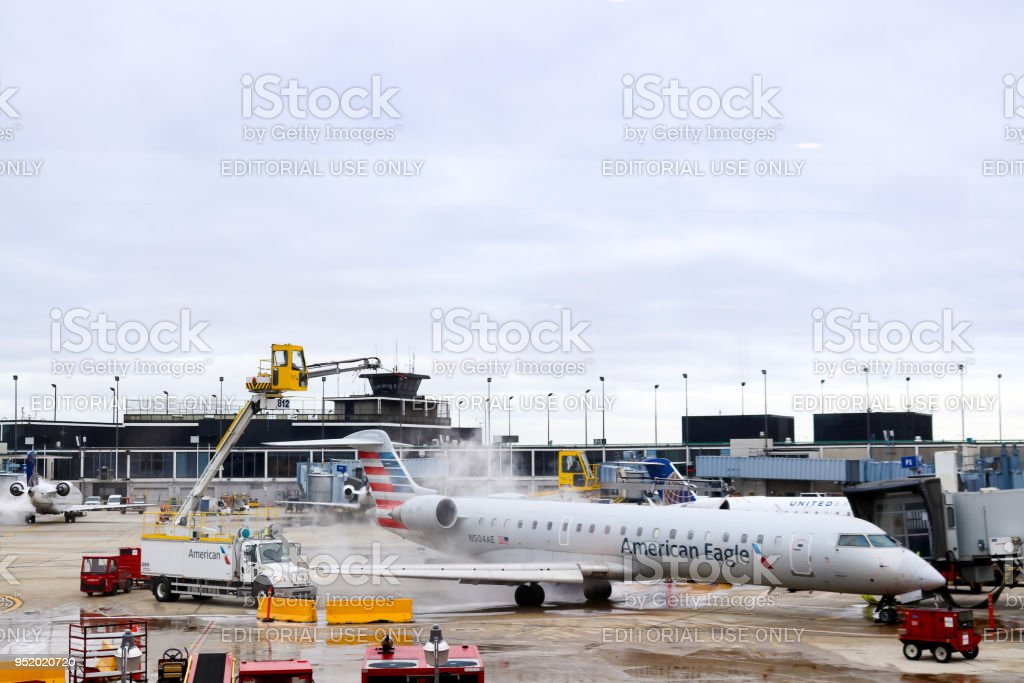 Machines with cranes de-ice an airplane wing at  OHare Airport in Chicago Illiniois stock photo