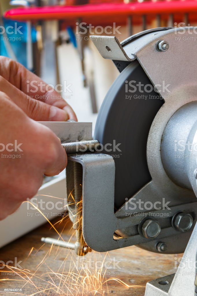 Machining of bolt on the grinding machine stock photo