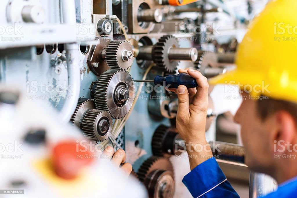 Machinist precisely setting up cog wheels stock photo
