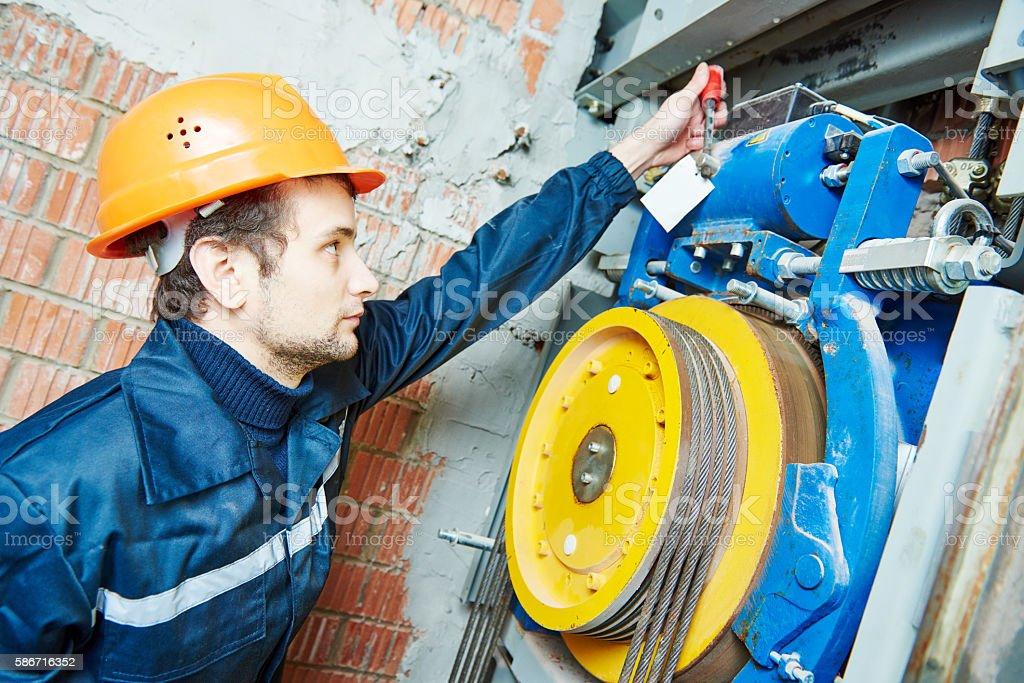 machinist worker adjusting elevator mechanism of lift – Foto