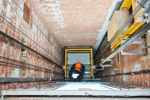 machinists adjusting lift in elevator hoist way – Foto