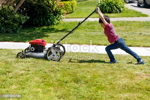 Stock photo of a small boy attempting to mow a lawn in a suburban neighborhood .