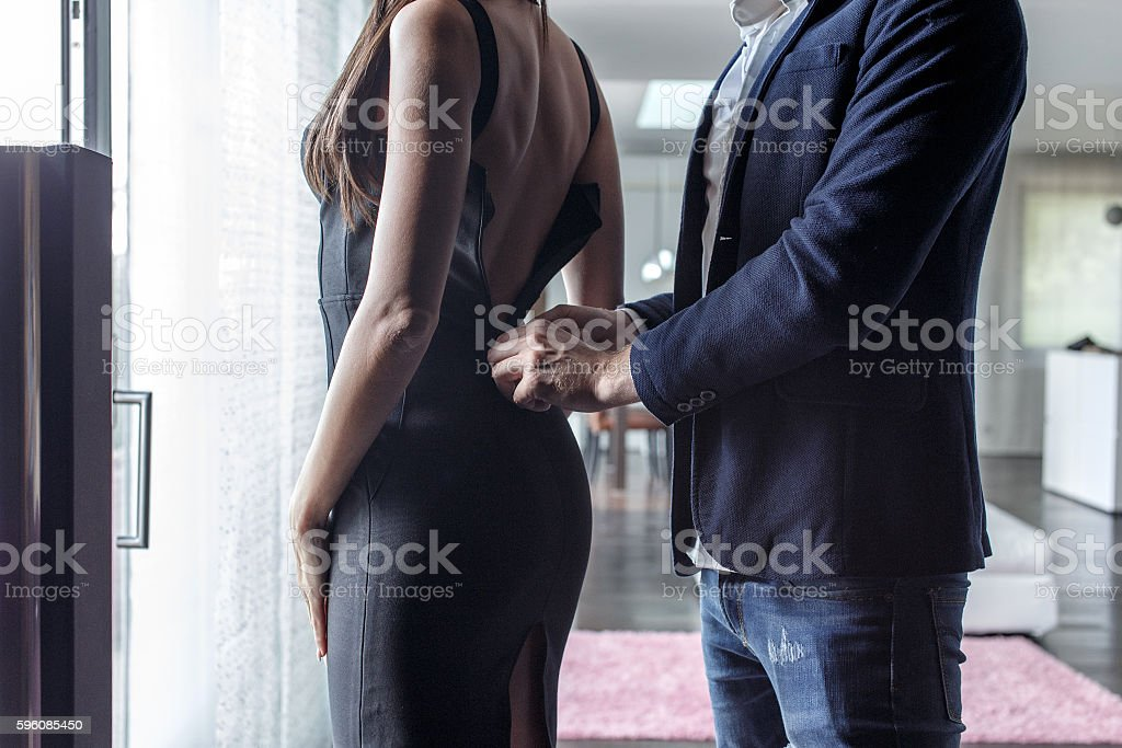 Macho man dressing woman into cocktail dress royalty-free stock photo