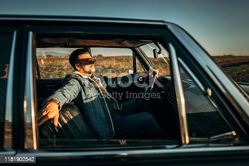 Young good-looking man driving in car alone, on country side, on sunny  day, in car from 1980 year