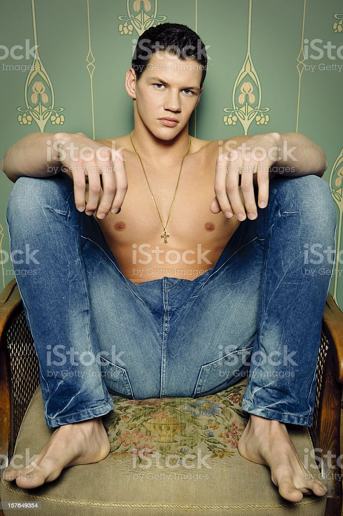 Macho man sitting in a old fashioned chair royalty-free stock photo