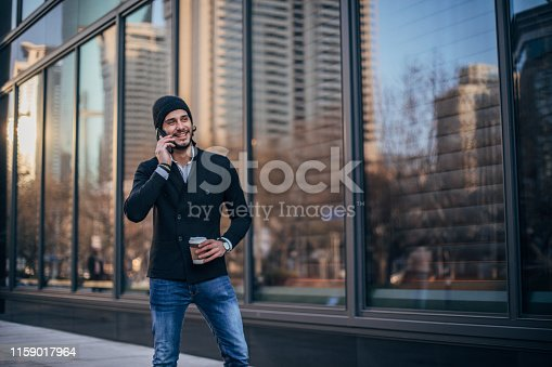 Handsome man in casual clothing standing on the street, holding takeout coffee and talking on smart phone.