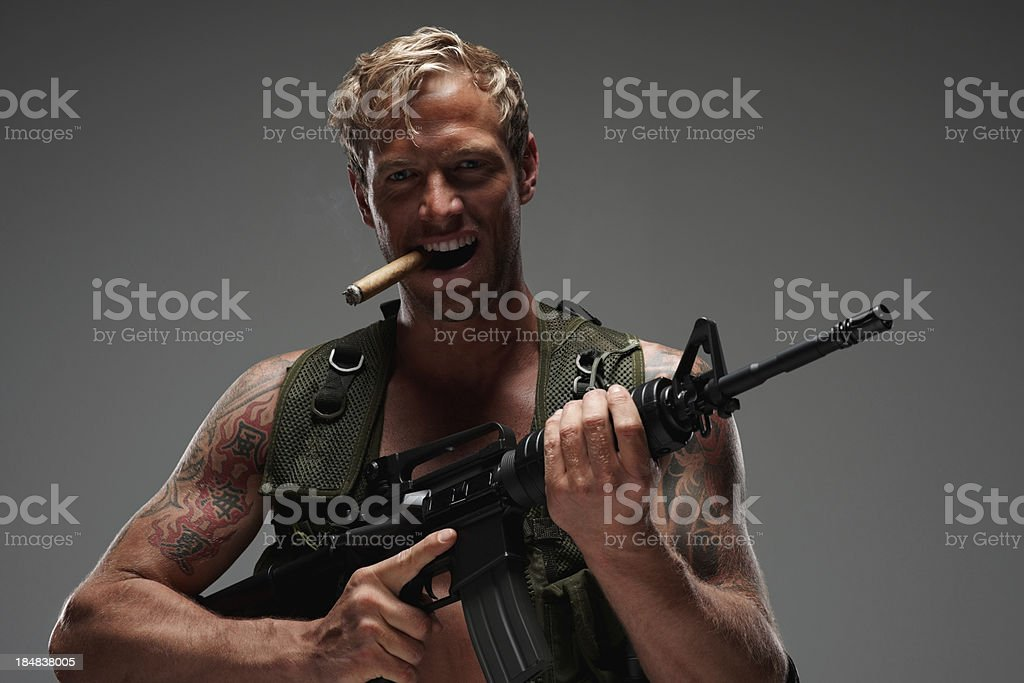 Macho man with an M16 assault rifle and smoking cigar royalty-free stock photo