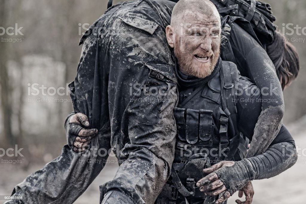 Macho shaven headed redhead male military swat security anti terror member carrying female team member during operations stock photo