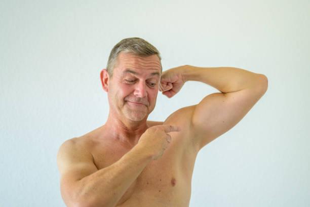 Macho shirtless man pointing to his biceps stock photo