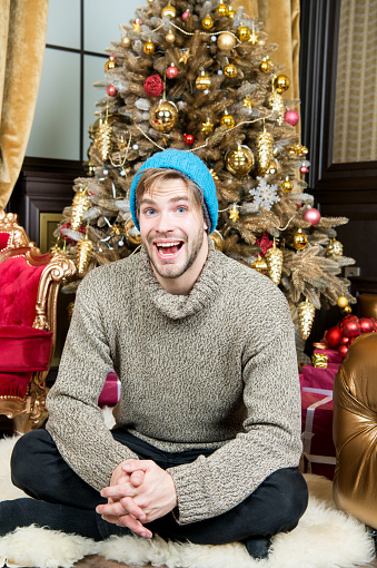 Macho smile on furry carpet at xmas tree in room