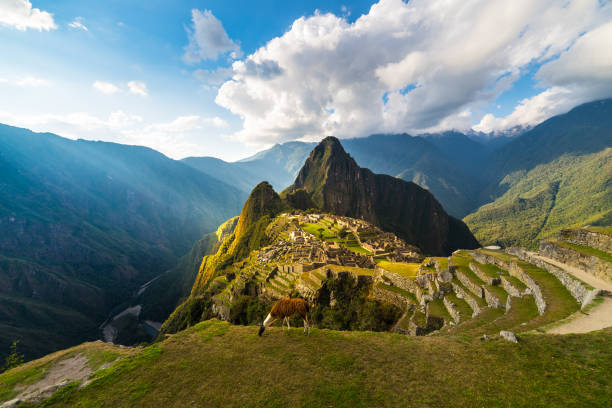 Machu Picchu illuminated by the warm sunset light. Wide angle view from the terraces above with scenic sky and sun burst. Dreamlike travel destination, world wonder. Cusco Region, Peru. stock photo