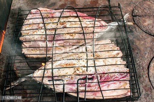 Mackerel fish grilling on rural outside fireplace