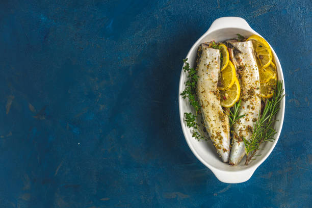 Mackerels served on white dish with lemon, thyme, rosemary and spices. Raw marinated fishes on classic blue surface. Seafood background. stock photo